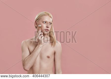 Young Caucasian Man With Long Fair Hair Using Quartz Roller For Cheek Massage While Standing On Pink