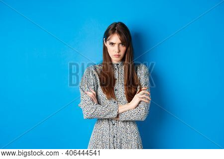 Angry Young Woman In Dress Feel Unfair, Cross Arms On Chest And Frowning Offended, Standing On Blue