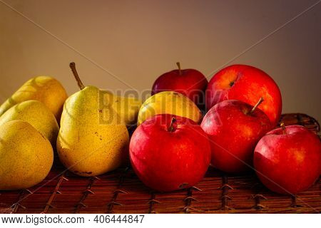 Several Ripe Yellow Pears And Red Apples Stand On A Wicker Basket Illuminated By Rays Of The Sun