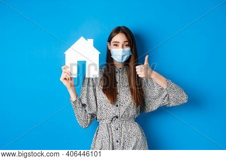 Real Estate, Covid-19 And Pandemic Concept. Cheerful Woman In Medical Mask Showing Paper House Cutou