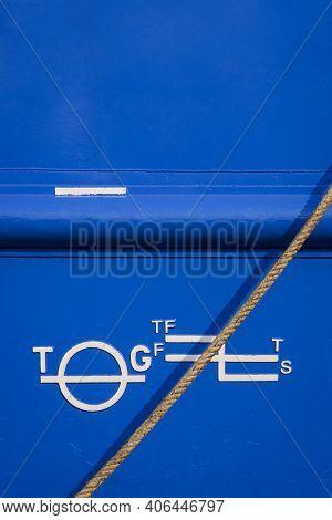 White Plimsoll Mark On Blue Rustproof Steel Hull Surface Of Large Vessel With Mooring Rope In Vertic