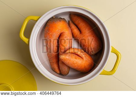 Three Trendy Ugly Carrots In Yellow Saucepan Ecology Concept