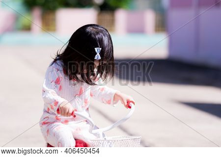 Cute Girl Bowed Her Head And Was Practicing Cycling. Children Do Morning Exercises After Waking Up.