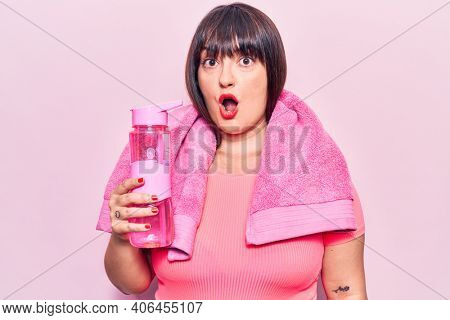 Young plus size woman wearing sportswear and towel holding water bottle scared and amazed with open mouth for surprise, disbelief face