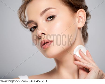 Beautiful face of a young Caucasian woman with a cotton pad in her hand, isolated.   Pretty white model takes care of her face. Removing makeup with a cotton swab