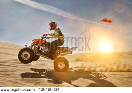 Portrait of man quad biking in dessert with lens flare