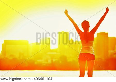 Success woman happy of joy winning with arms up in sunset. Fitness exercise weight loss goal achievement win. Athlete healthy girl silhouette on warm sun flare summer day city skyline background.