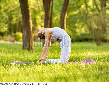 Female Workout On Yoga Mat. Adult Woman Practising Yoga. Sporty Young Woman Doing Yoga At Park In Th