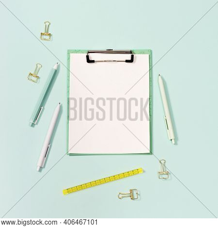 Paper Tablet With Clip And Stationery. Blue And White Colored Pens, Yellow Ruler And Modern Paper Cl