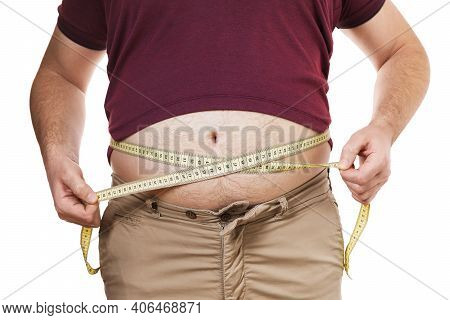 Overweight Man Measures His Waist With A Measuring Tape, Isolated On White Background. Concept On Th