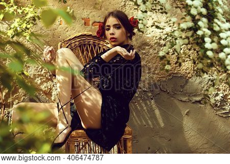 Girl Tying Shoe Laces On Wicker Chair On Sunny Day. Stylish Model In Fashionable Black Dress, Red Li
