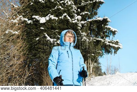 Pensioner With Poles For Nordic Walking Outdoors. Elderly Woman Wearing Glasses On Winter Sunny Day.