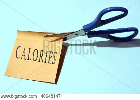 Scissors That Cut Yellow Notepad With Calories Text On A Blue Background. Diet Concept