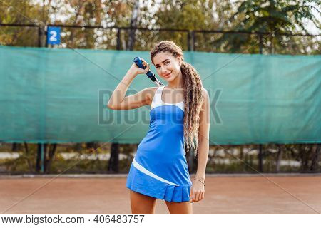 Beautiful Woman Posing On A Clay Tennis Court After The Game. An Attractive, Sexy Lady In A Short Te