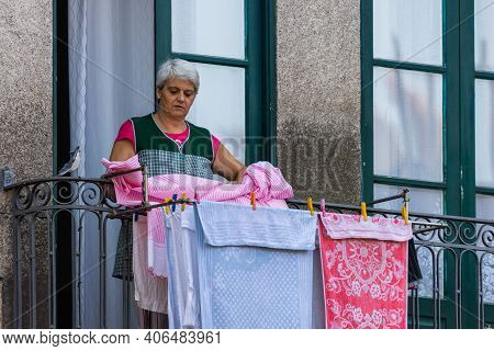 Porto, Portugal - October 06, 2018: Unidentified Women Dry Linen On The Balcony Of Traditional House