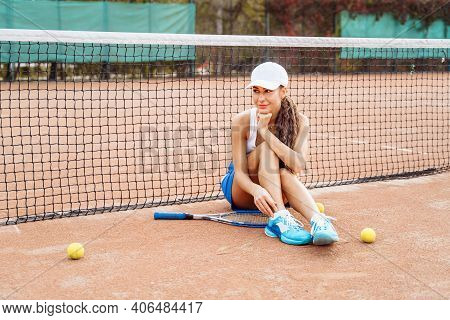 Attractive Tennis Player Of European Appearance In Tennis Clothes Sitting On A Tennis Court. Posing