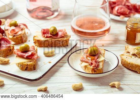 Appetizers and open sandwiches with Italian antipasti, camembert, Parma ham and rose wine on wooden table