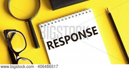 Notepad With The Text Response On A Yellow Background With Glasses, A Magnifying Glass And A Pencil.