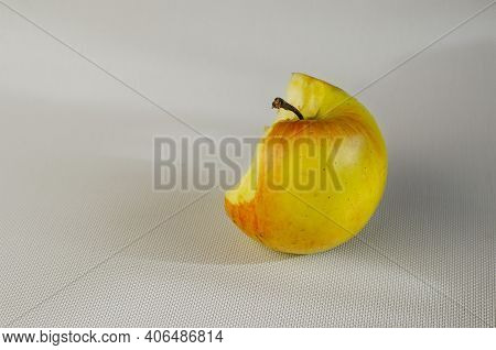 A Half-eaten Apple On A White Background. A Bitten Ripe Apple On A White Background. Selective Focus