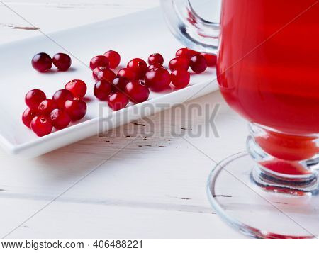 Selective Focus On Cranberries On A White Rectangular Ceramic Plate. Red Cranberry Drink In A Glass