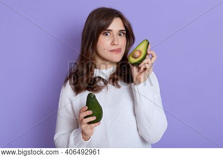 Portrait Of Girl With Pleasant Appearance, Woman With Two Avocado Parts In Hands Isolated Over Lilac