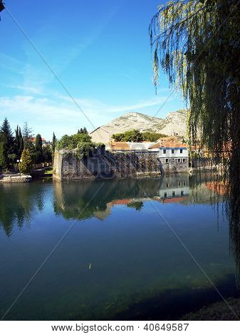 Mirror image of the old buildings in the town of Trebinje Bosnia and Herzegovina in the water of the river. poster