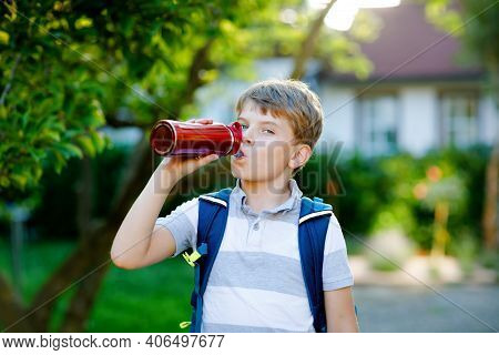 Happy Little Kid Boy Drinking From Water Bottle And Backpack Or Satchel. Schoolkid On Way To School.