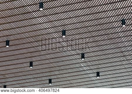Bright Halogen Spotlight On The Ceiling Grille. Abstract Background.