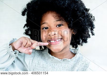 Portrait Images Of Mixed Race Girl, 5 Years Old, Smiling Brightly And Showing Broken Milk Tooth, Wit