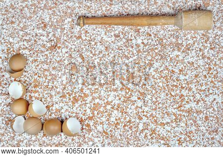 A Broken Eggshell On A Table And A Wooden Mortar In The Opposite Place In The Picture Against The Ba