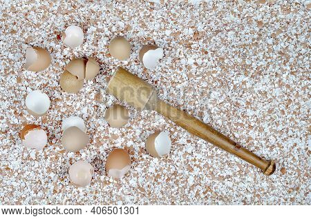 Broken Eggshells Scattered On The Table, Wooden Mortar On The Background Of Crushed Eggshells.