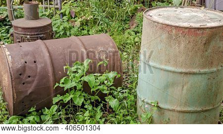 A Pile Of Old Rusty Metal Barrels And A Stove In The Backyard Of A Rural House Close-up On The Grass