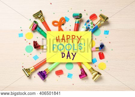 Card With Text Happy Fool's Day And Party Blowers On Wooden Background, Flat Lay