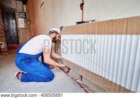 Male Plumber In Work Overalls Installing Heating Radiator In Empty Room. Bearded Young Man In Safety