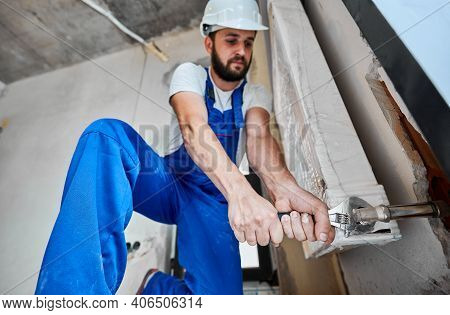 Low Angle Of Bearded Young Man In Safety Helmet Using Adjustable Wrench While Installing Heating Rad