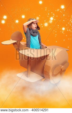 Cute dreamer girl playing with a cardboard airplane, purposefully looking into the distance. Childhood. Fantasy, imagination. Studio portrait on a yellow background with stars and clouds.