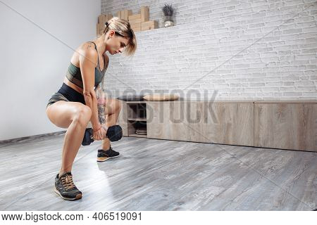 Athletic Young Blonde Woman Doing Heavy Dumbbell Exercise In Gym. Female Doing Squats.