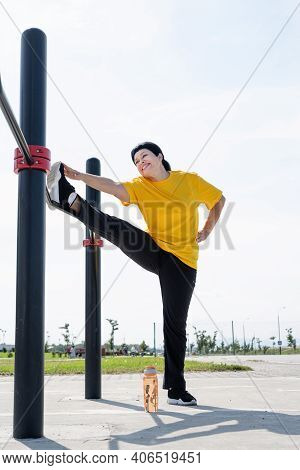 Senior Woman Stretching Her Legs Outdoors On The Sports Ground