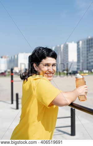 Smiling Senior Woman Having Rest After Workout Outdoors On The Sports Ground Bars