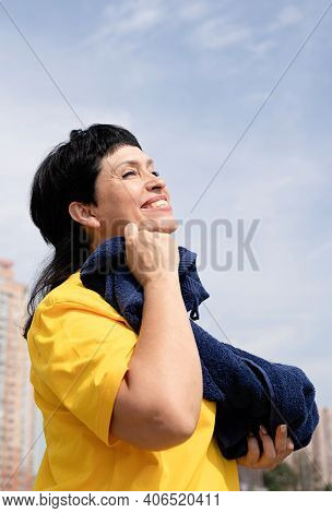 Smiling Senior Woman Wiping Out Sweat After Hard Workout Outdoors In The Park