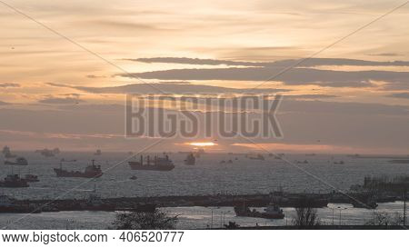Sea Port For Cargo Ships On Background Of Sunset. Action. Many Different Ships Float In Sea Off Coas