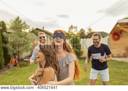Group Of Cheerful Young Friends Having Fun At Summertime Outdoor Party, Playing Blind Man's Buff, Ru