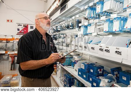 Store Manager Doing Inventory Inside Of A Diy Electrical Wholesale Retail Shop