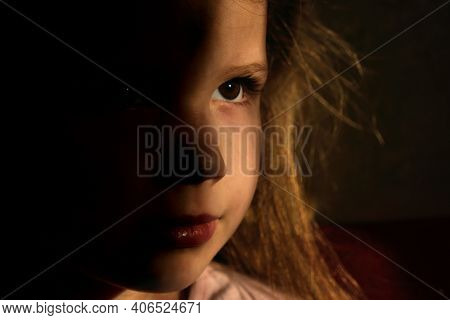 Powerful Low Key Image Of Little Girl In Dark Side With Shadow On Face With Blissful Eyes  Looking U