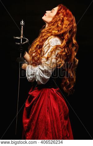 Profile portrait of a beautiful and brave red-haired woman with a battle epee (rapier) on a black background. Historical reconstruction of the 16-17th centuries.