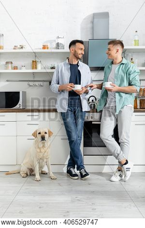 Full Length Of Cheerful Homosexual Men Holding Cups And Standing Near Dog In Kitchen.