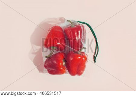Reusable Packaging Of Products By Weight. Red Bell Peppers In A Reusable Bag On A Pink Background.
