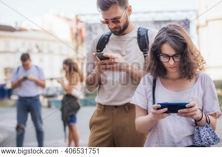 Group Of Friends Using Smartphones Together. Young People Addiction To New Technology Trends. Youth,