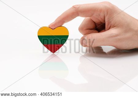 Love And Respect Lithuania. A Man's Hand Holds A Heart In The Shape Of The Lithuanian Flag On A Whit