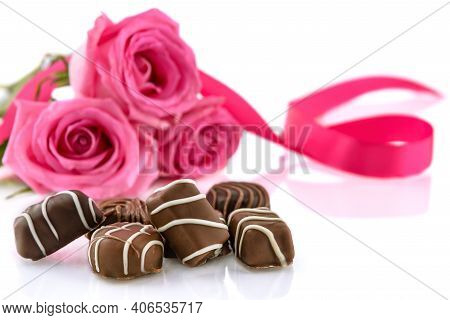 Chocolate Pralines And Bouquet Of Pink Roses On The White Background. Valentine's Day And Women's Da
